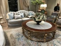 Living-room-with-a-baroque-rococo-design-velvet-sofa-and-round-sumptuous-coffee-table