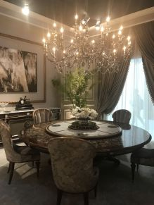 sumptuous-round-dining-table-with-a-swivel-lazy-susan-top-and-chandelier-over