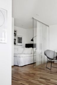 a-Nordic-bedroom-with-a-bed-and-some-black-and-white-artworks-separated-from-the-rest-of-the-apartment-with-a-glass-sliding-door
