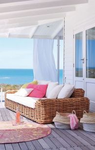 a-beach-terrace-with-a-wooden-deck-a-large-wicker-sofa-bright-and-white-pillows-baskets-and-a-bright-rug