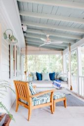 a-beachy-porch-in-light-blues-and-white-with-a-hanging-daybed-and-a-lounger-some-pillows-rugs-and-lamps