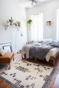 a-boho-spring-bedroom-with-a-wooden-bed-a-leather-chair-blue-and-white-bedding-a-printed-rug-potted-greenery