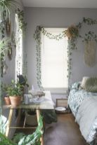 a-boho-spring-bedroom-with-lots-of-potted-greenery-macrame-and-botanical-bedding
