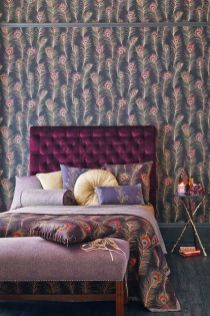 a-bold-bedroom-with-a-peacock-feather-wall-a-bold-purple-bed-and-a-purple-bench-colorful-pillows-and-a-nightstand