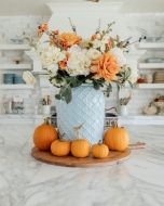 a-bold-modern-centerpiece-of-a-blue-jar-white-and-orange-blooms-and-orange-pumpkins-around-for-Thanksgving