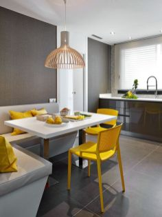 a-bold-modern-dining-nook-in-the-kitchen-with-a-corner-seat-a-table-bright-yellow-chairs-and-a-pretty-lamp