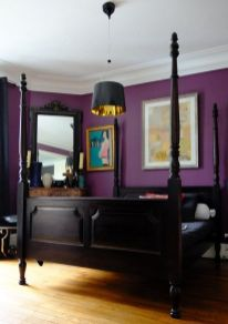 a-bold-purple-bedroom-with-very-dark-furniture-a-non-working-fireplace-and-a-mirror-a-pendant-lamp-and-bold-artworks