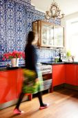 a-bold-red-kitchen-with-a-blue-patterned-tile-wall-a-glass-cabinet-and-a-refined-and-chic-chandelier-over-the-space