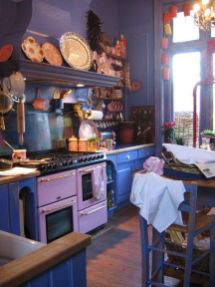 a-bold-retro-kitchen-with-purple-cabinets-pink-appliances-gold-handles-and-open-shelves-with-pretty-objects-on-display-is-wow