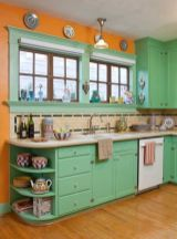 a-bold-retro-ktichen-in-green-with-orange-walls-a-neutral-and-black-tile-backsplash-and-decorative-plates-on-the-wall