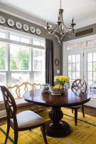 a-bold-vintage-dining-room-with-grey-walls-a-large-window-a-heavy-round-table-and-chairs-decorative-plates-and-a-bold-yellow-rug