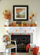 a-bright-Thanksgiving-mantel-with-colorful-leaves-colorful-striped-candles-bright-cubes-dried-leaf-arrangements-and-blankets-and-pillows