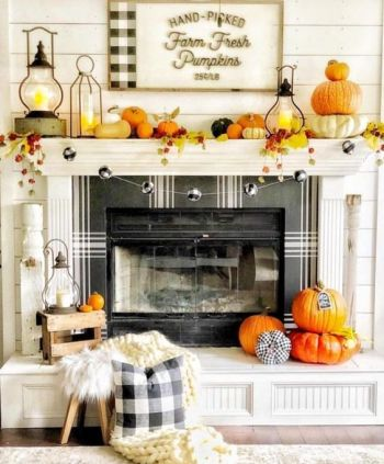 a-bright-and-fun-Thanksgiving-mantel-with-bold-pumpkins-bright-leaves-candle-lanterns-and-a-plaid-ball-garland
