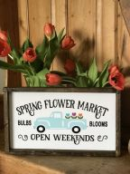 a-bright-and-fun-spring-sign-with-a-pastel-truck-and-blooms-and-letters-in-a-simple-stained-wooden-frame