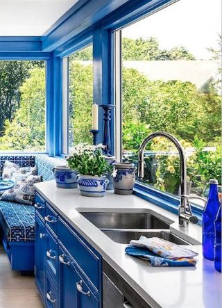 a-bright-blue-kitchen-with-bold-walls-and-cabinetry-white-countertops-and-patterned-blue-and-white-plants