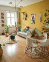 a-bright-boho-living-room-with-a-yellow-accent-wall-neutral-furniture-books-potted-plants-touches-of-greenery-and-a-jute-rug