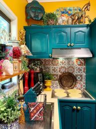 a-bright-kitchen-with-teal-cabinets-mismatching-tile-backsplash-colorful-accessories-and-bold-accents-is-fun