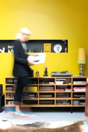 a-bright-living-room-with-a-shiny-yellow-accent-wall-a-niche-shelf-a-vintage-sideboard-and-a-bold-yellow-table-lamp