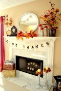 a-bright-rustic-Thanksgiving-mantel-with-bold-leaf-arrangements-pumpkins-on-stands-some-banners-and-candles-in-candleholders