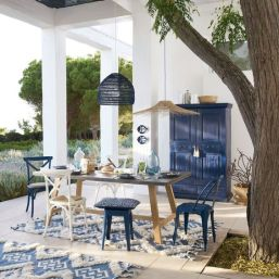 a-bright-seaside-patio-in-blue-and-white-with-a-wooden-table-and-white-and-navy-chairs-and-stools-pendant-lamps-and-a-navy-sideboard