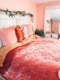 a-bright-spring-bedroom-with-coral-and-pink-bedding-faux-greenery-and-blooms