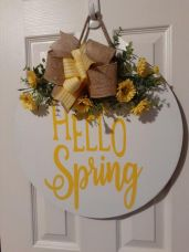 a-bright-spring-sign-with-a-striped-and-burlap-bow-bright-yellow-blooms-and-greenery-and-yellow-letters