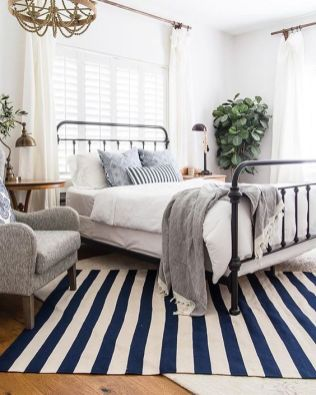 a-bright-vintage-farmhouse-bedroom-with-a-metal-bed-vintage-furniture-grey-and-blue-bedding-potted-plants-and-a-beaded-chandelier