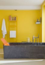 a-bright-yellow-bathroom-with-a-concrete-tub-a-yellow-ladder-shelves-and-neutral-textiles-is-very-modern-and-bold