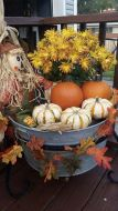a-bucket-with-bold-blooms-leaves-pumpkins-and-a-scarecrow-is-a-pretty-outdoor-decoration-for-Thanksgiving