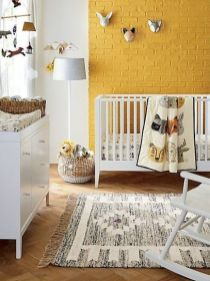 a-cheerful-nursery-with-a-yellow-brick-wall-white-furniture-a-printed-rug-funny-taxidermy-and-a-mobile-plus-baskets