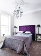 a-chic-bedroom-with-a-bright-purple-bed-dark-nightstands-and-lamps-a-catchy-vintage-chandelier-and-grey-and-purple-bedding