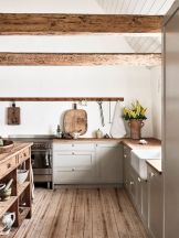 a-chic-contemporary-kitchen-in-dove-grey-with-a-wooden-kitchen-island-and-countertops-and-rough-wooden-beams