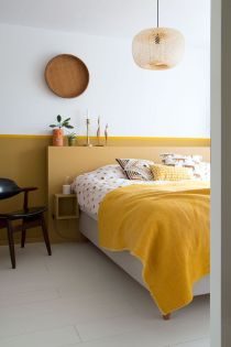 a-chic-contemporary-living-room-with-a-mustard-accent-wall-a-yellow-and-grey-bed-bold-yellow-bedding-a-wooden-plate-and-a-wicker-lamp