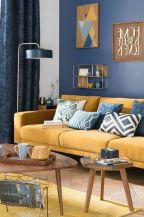 a-chic-living-room-with-a-navy-wall-a-yellow-sofa-and-a-rug-printed-pillows-a-cool-gallery-wall-and-wooden-tables