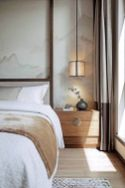 a-chic-neutral-bedroom-with-mountain-panels-on-the-walls-a-wooden-nightstand-and-an-upholstered-bed-pendant-lamps-and-color-block-curtains