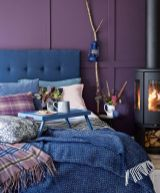 a-colorful-bedroom-with-deep-purple-panel-walls-a-blue-bed-and-blue-bedding-a-hearth-and-a-lamp-on-a-branch