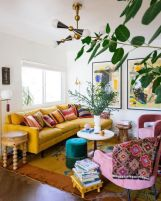 a-colorful-boho-living-room-with-a-yellow-sofa-and-a-rug-pink-chairs-bold-printed-textiles-a-green-ottoman-wooden-stools-and-tables