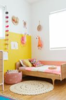 a-colorful-girls-room-with-a-color-block-yellow-wall-a-simple-bed-and-pink-bedding-a-pink-basket-cardboard-flamingo-heads-and-other-decor