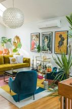 a-colorful-mid-century-modern-living-room-with-a-mustard-sofa-a-bold-rug-teal-chairs-a-bright-gallery-wall-and-potted-plants