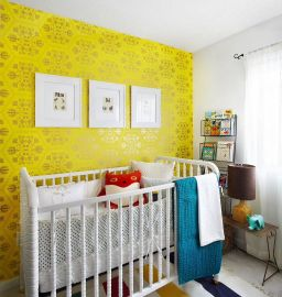 a-colorful-nursery-with-a-bold-yellow-wallpaper-wall-a-white-crib-wire-shelf-colorful-textiles-and-bedding-plus-a-gallery-wall