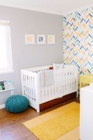 a-colorful-nursery-with-a-bright-geometric-wall-white-and-yellow-furniture-a-yellow-rug-a-blue-ottoman-and-a-gallery-wall