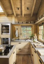 a-contemporary-wooden-chalet-kitchen-with-concrete-countertops-skylights-wooden-beams-on-the-ceiling-is-chic-and-light-filled