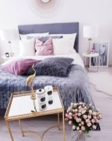 a-cool-feminine-bedroom-with-a-purple-bed-a-gold-nightstand-with-candles-pink-blooms-pink-white-and-purple-pillows