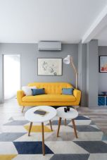 a-cool-mid-century-modern-living-room-with-grey-walls-a-yellow-sofa-round-tables-a-floor-lamp-and-a-geo-rug