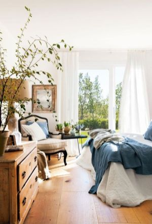 a-country-spring-bedroom-with-vintage-furniture-blue-bedding-greenery-and-potted-plants-a-mirror-in-a-wooden-frame
