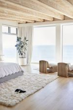 a-cozy-and-stylish-contemporary-bedroom-with-catchy-bent-wooden-loungers-a-bed-a-white-fur-rug-and-a-statement-plant-plus-sea-views