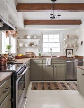 a-cozy-modern-farmhouse-kitchen-with-green-cabinetry-wooden-countertops-and-wooden-beams-that-match-and-warm-up-the-space