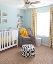 a-cozy-nursery-with-light-blue-walls-a-white-crib-a-grey-chair-yellow-linens-and-ledges-with-books-and-artworks