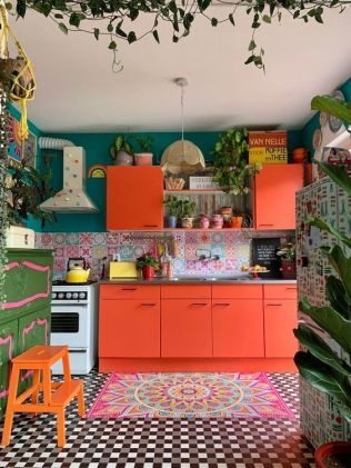 a-crazily-colorful-kitchen-with-orange-cabinets-a-colorful-tile-backsplash-a-bold-rug-emerald-walls-and-bold-furniture