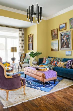 a-crazily-colorful-living-room-with-yellow-walls-a-navy-sofa-a-pink-ottoman-and-a-purple-chair-colorful-rugs-pillows-and-upholstery